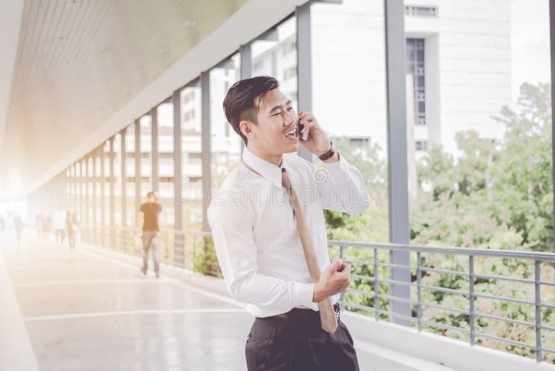谈话亚洲的商人是微笑的电话电话并且放松,在董事之间的会议 在等待在边路之间 免版税图库摄影