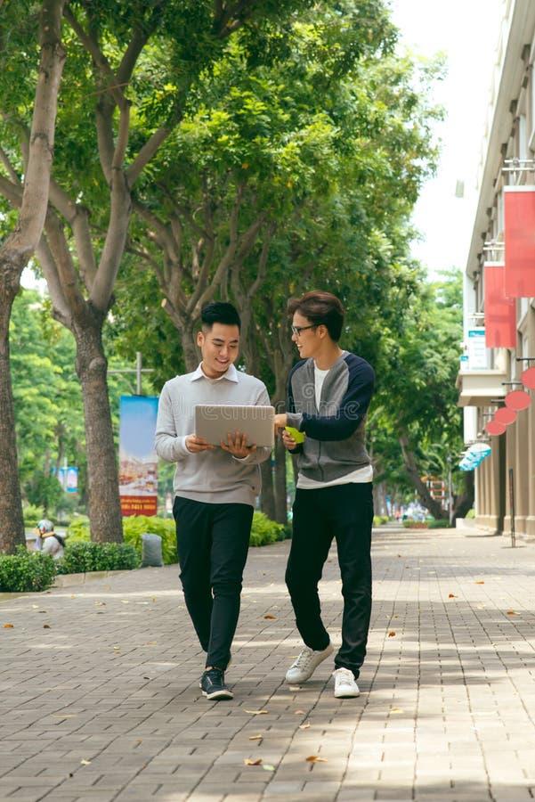 谈话企业的同事,当走在办公楼前面时 免版税图库摄影