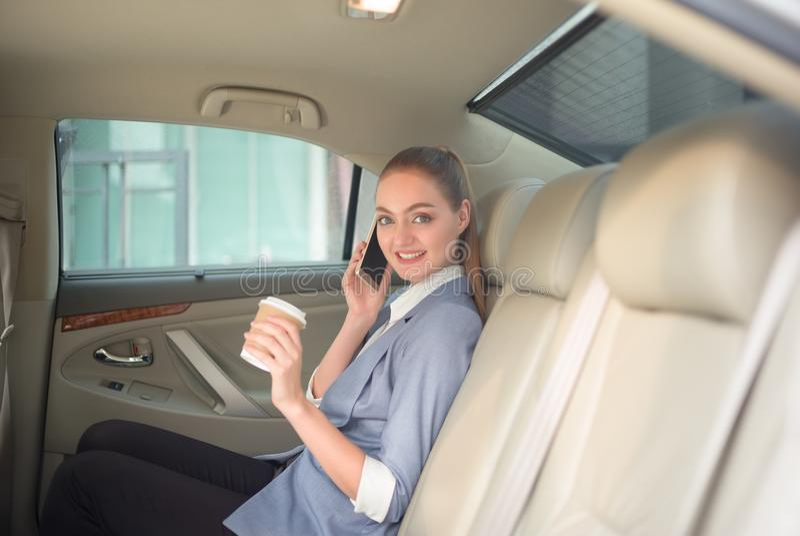 谈话使用电话和举行h的美丽的年轻女商人 库存图片