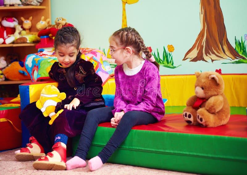 谈话和使用在孩子的幼儿园的逗人喜爱的女孩与特别需要 免版税图库摄影
