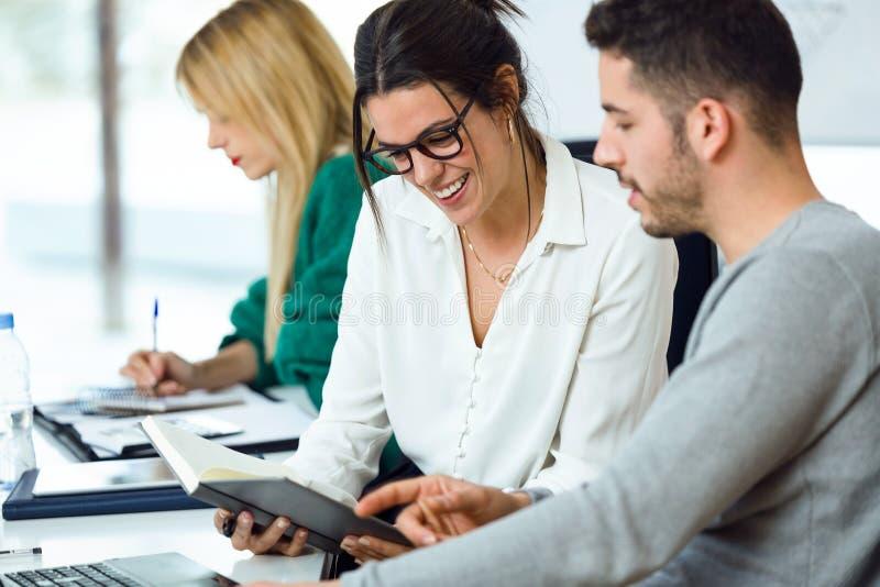 谈话和写关于工作的年轻小组买卖人在coworking的地方 库存图片