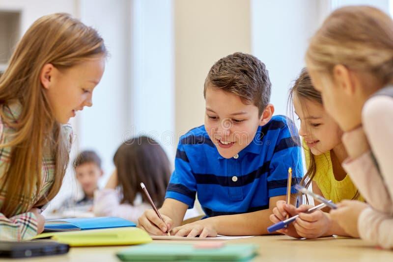 谈话和写在学校的小组学生 免版税图库摄影