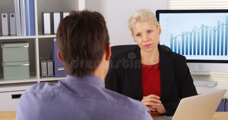 谈话和听在办公室的企业同事 库存照片