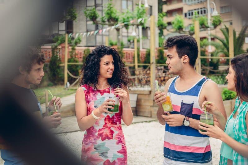 谈话和喝在夏天党的青年人 免版税图库摄影