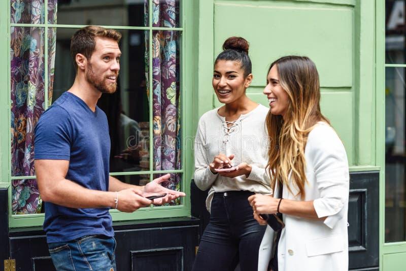 谈话和微笑户外与巧妙的电话的三不同种族的人在他们的手上 多种族小组都市的朋友 免版税库存图片