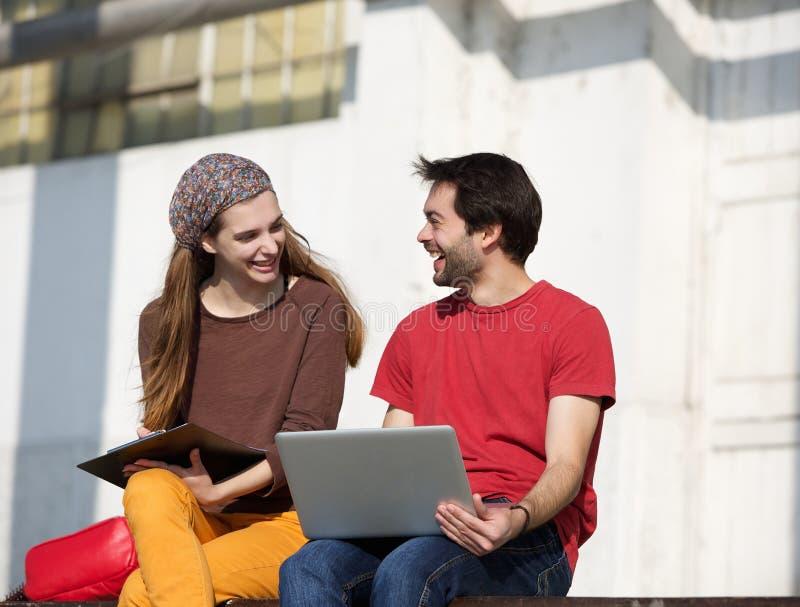 谈话和研究户外膝上型计算机的两位大学生 免版税库存图片