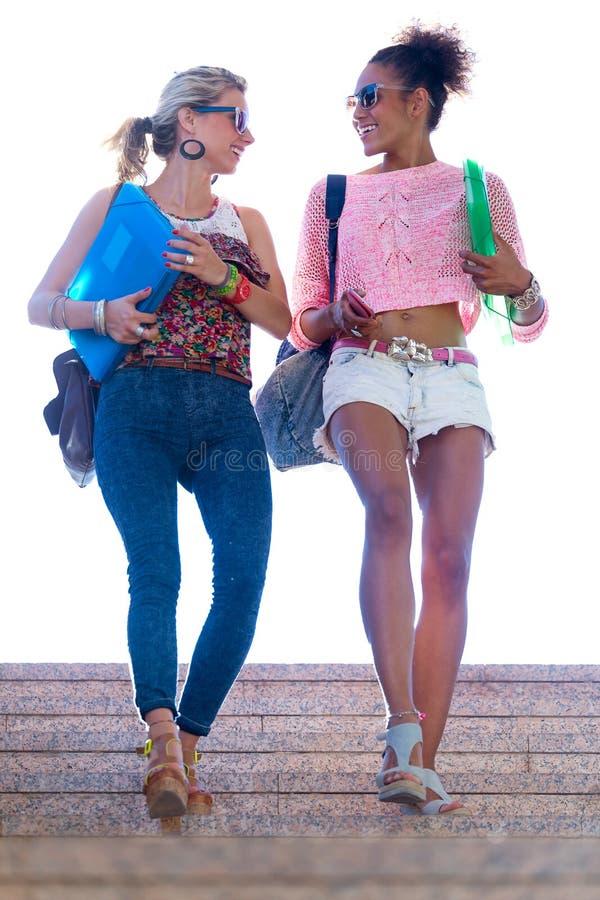 谈话和笑在台阶的两个女孩 免版税库存照片
