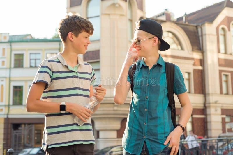谈话和笑在城市街道上的两个朋友男孩少年13,14岁室外画象  免版税库存图片