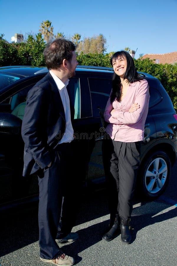 谈话和笑在汽车前面的两个商人 库存图片