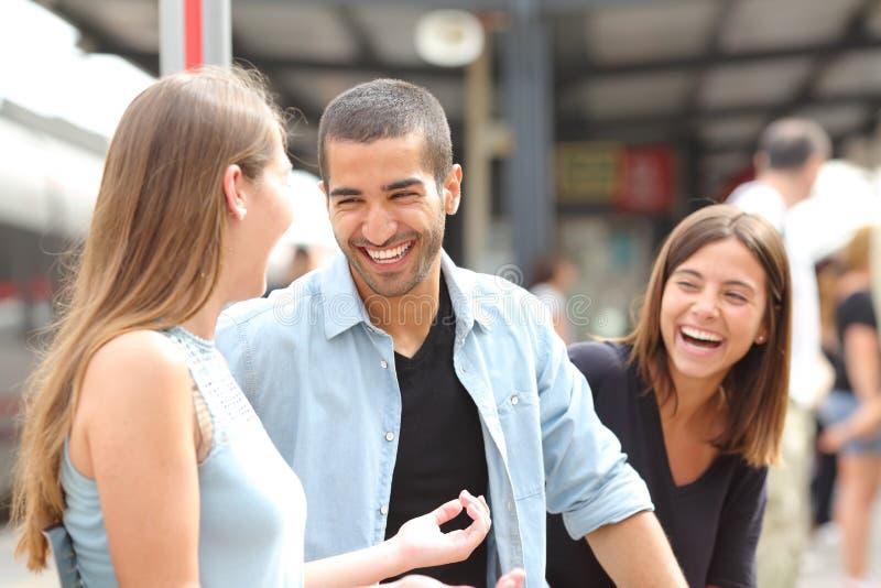 谈话和笑在火车站的三个朋友 免版税库存照片