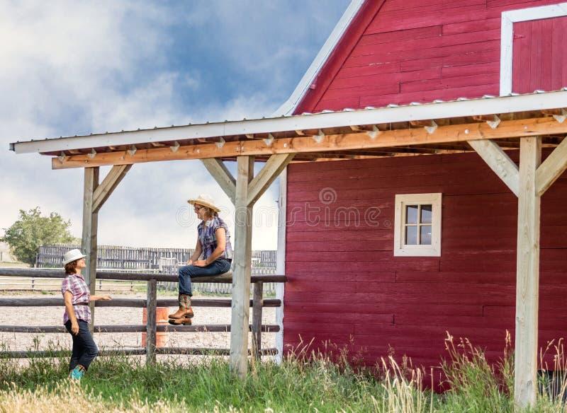 谈话和笑由一个红色谷仓的两个女牛仔 免版税库存照片
