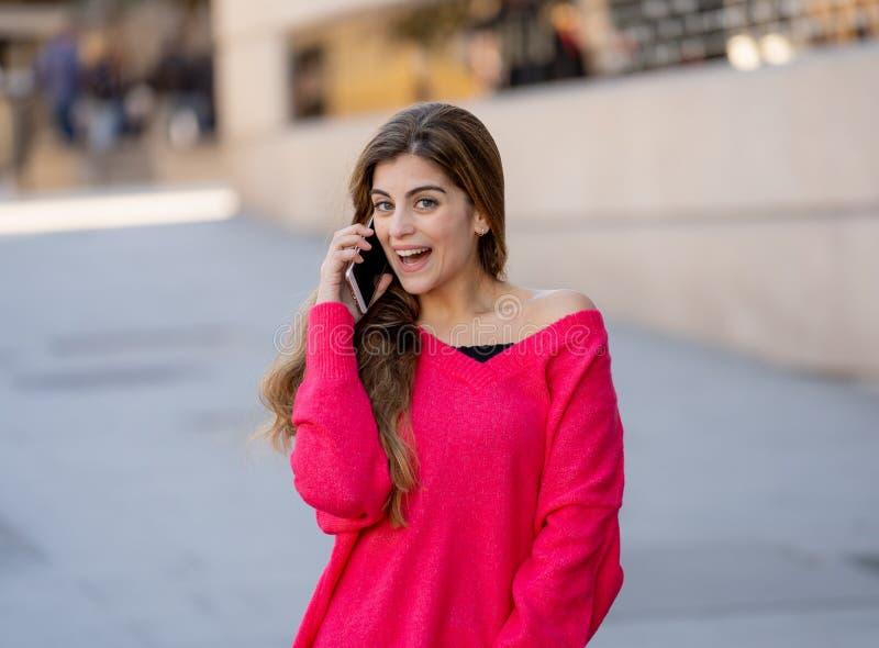 谈话和聊天在她的智能手机的可爱的年轻学生妇女外面在欧洲城市 免版税库存照片