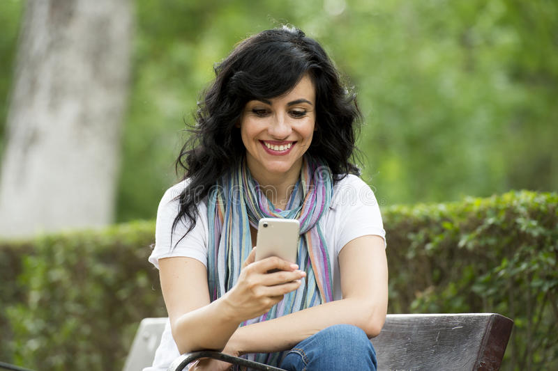 谈话和texing在她巧妙的电话的愉快的可爱的拉丁妇女 图库摄影