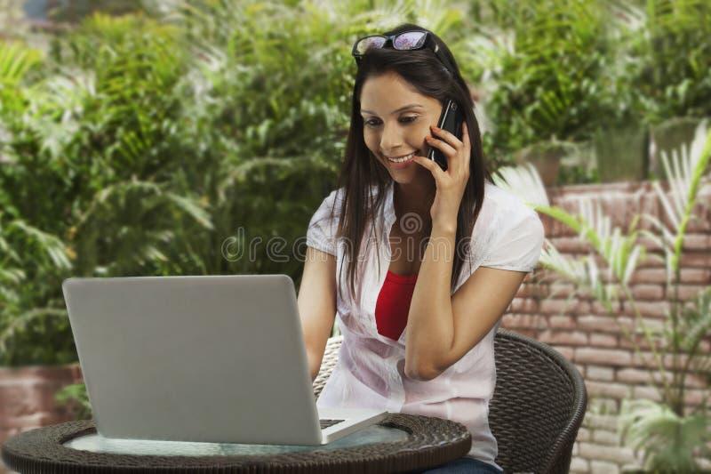 谈话在一个手机和使用膝上型计算机的妇女 免版税库存照片
