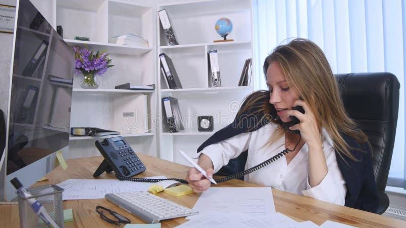 谈话在手机和做在笔记本的年轻女商人笔记,当坐在桌上在办公室时 免版税库存图片