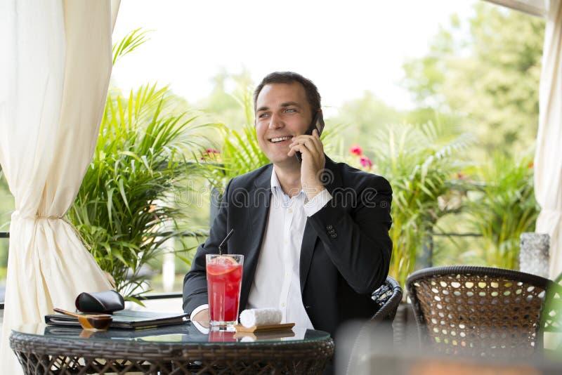 谈话在手机和喝鸡尾酒的商人 免版税库存图片