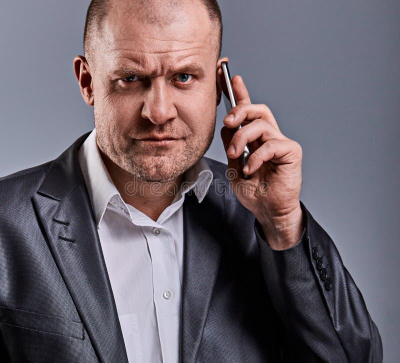 谈话在手机和在手中拿着在办公室衣服的不快乐的疲乏的恼怒的商人另外一个电话在灰色演播室 库存图片