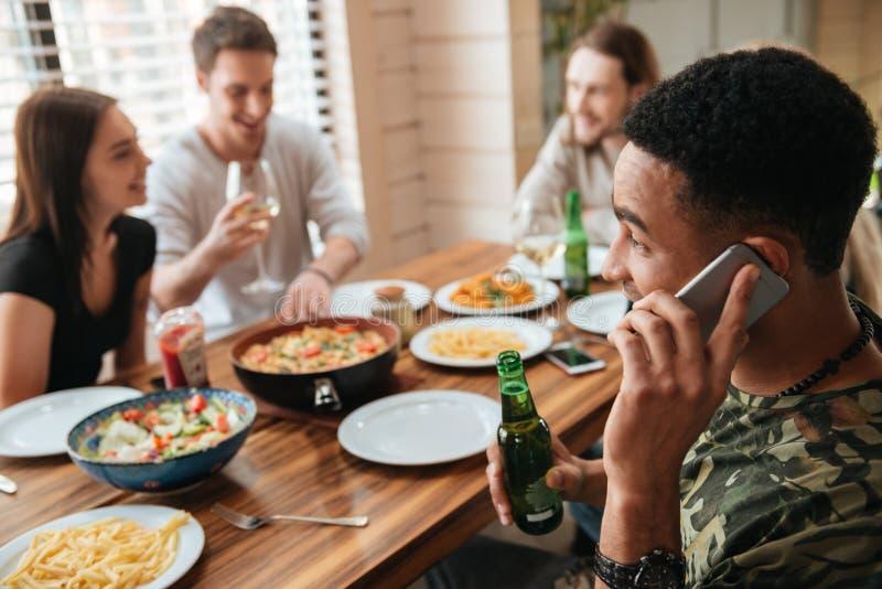 谈话在手机和庆祝与朋友的微笑的人 免版税图库摄影
