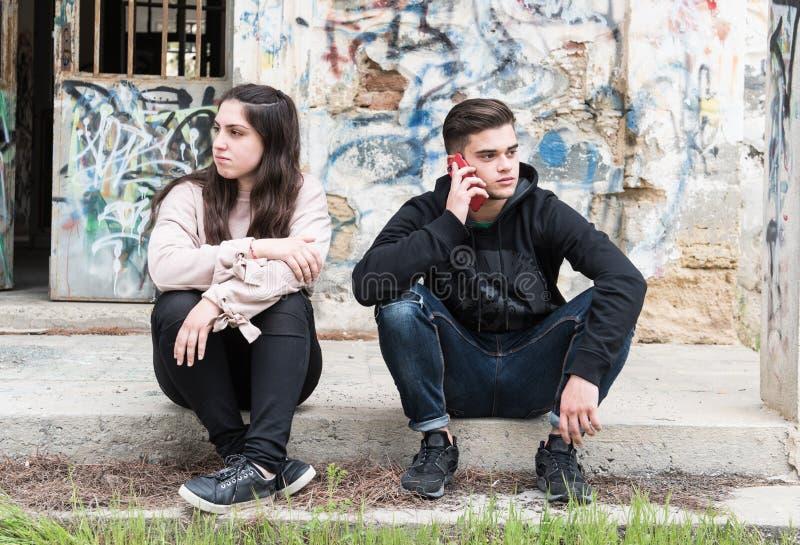 谈话在手机和忽略g的年轻十几岁的男孩 库存图片