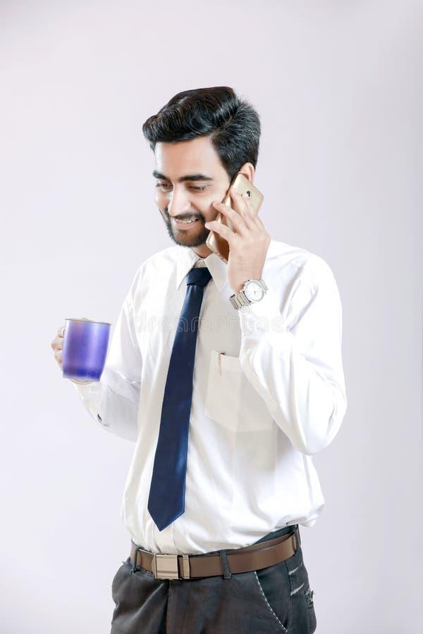 谈话在手机和拿着杯子的印地安年轻人手中 库存照片
