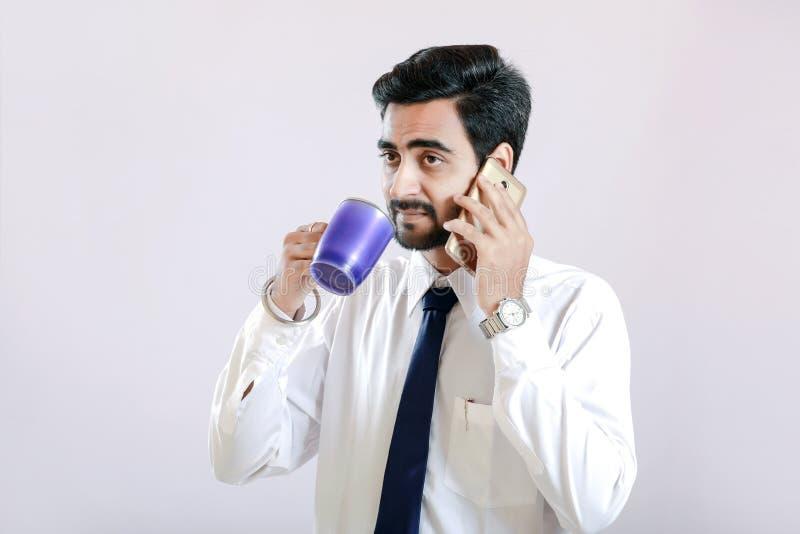 谈话在手机和拿着杯子的印地安年轻人手中 免版税库存照片