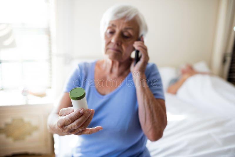 谈话在手机和拿着医学处方瓶的妇女在卧室 免版税库存图片