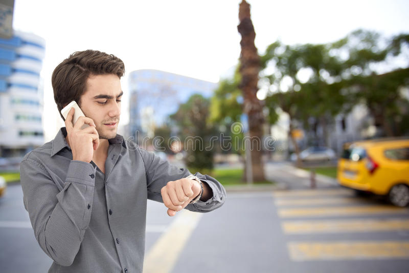 谈话在手机和看在街道上的年轻商人手表 免版税图库摄影