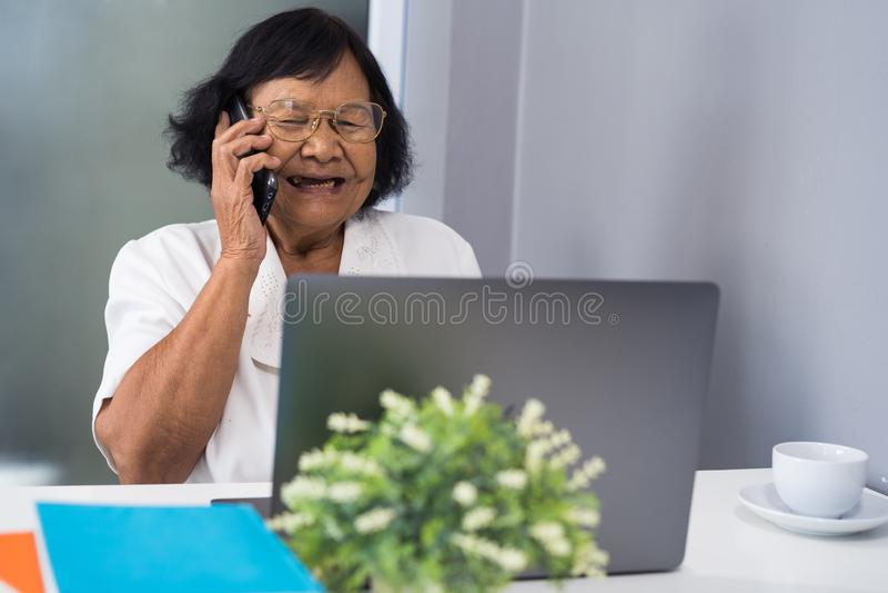 谈话在手机和研究膝上型计算机的愉快的资深妇女 免版税图库摄影