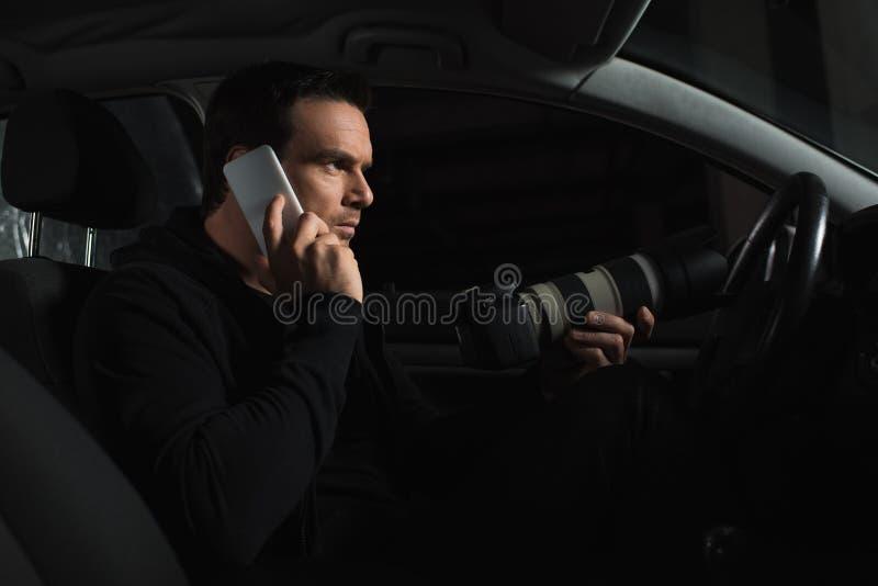 谈话在智能手机和做监视的男性私有detceitve由从他的照相机 免版税库存照片