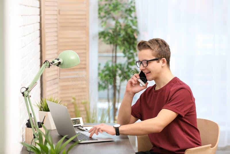 谈话在电话和使用膝上型计算机的英俊的十几岁的男孩在桌上 免版税库存照片