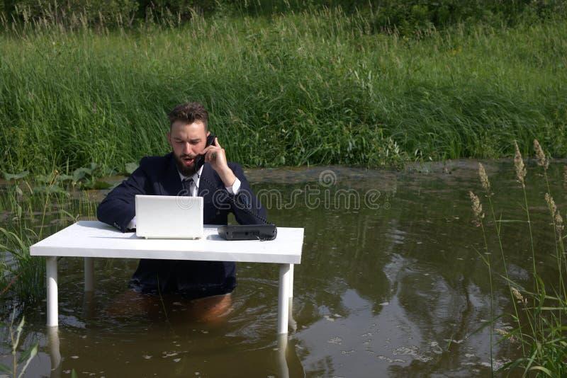 谈话在电话和使用计算机的英俊的年轻人,当工作时 库存图片