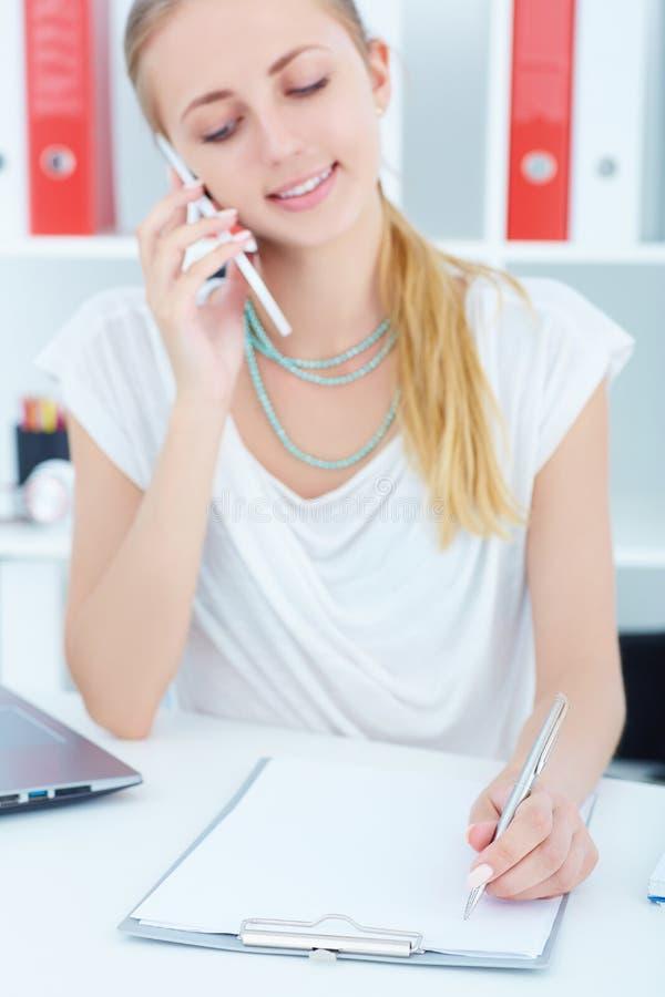 谈话在电话和写笔记的年轻白种人女实业家在办公室 在文件的焦点 库存图片