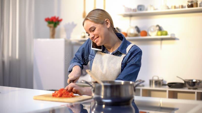谈话在电话和准备西红柿酱,容易的食物食谱的年轻女人 免版税库存照片