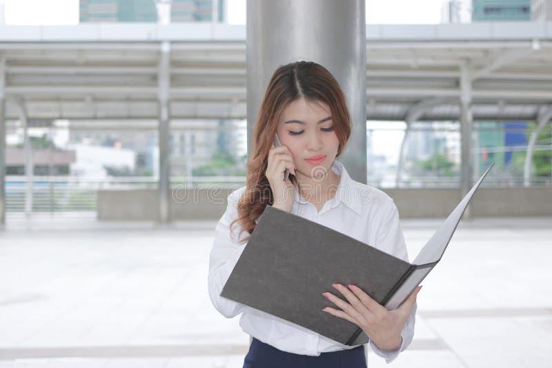 谈话在电话和在她的手上的相当年轻亚裔女商人正面图看文件外部办公室 图库摄影