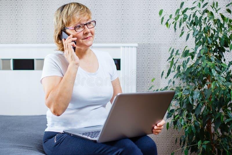 谈话在电话和在家研究膝上型计算机的一名中年妇女 免版税库存照片