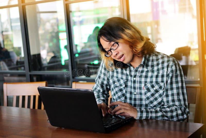 谈话在电话和工作反对他的膝上型计算机的英俊的年轻亚裔雇员画象在办公室 免版税库存照片
