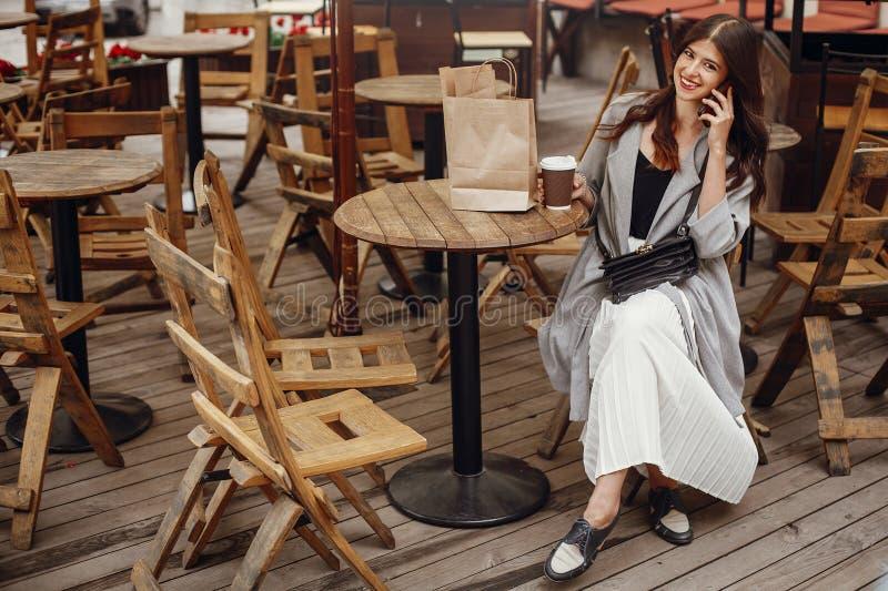 谈话在电话和微笑,与杯子的华美的年轻女人c 免版税库存图片