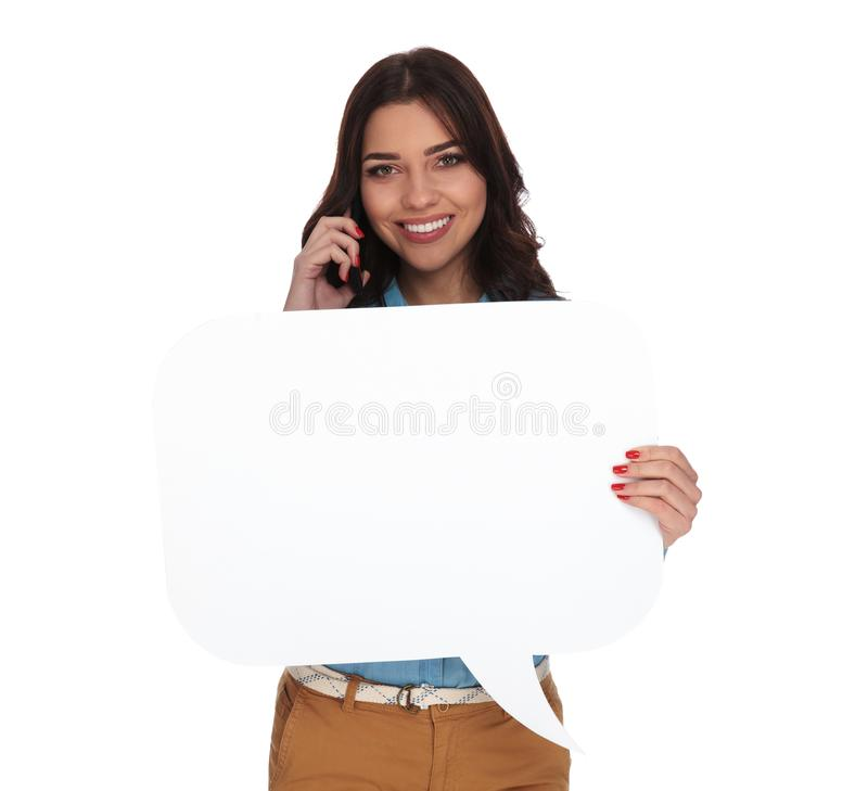 谈话在电话和拿着讲话泡影的妇女 免版税库存照片