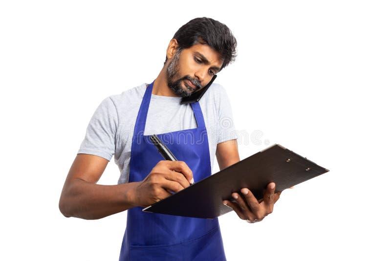 谈话在电话和检查剪贴板的大型超级市场雇员 免版税图库摄影