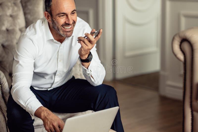 谈话在电话和研究膝上型计算机的商人,当坐在酒店房间时 工作从酒店房间的微笑的商人  库存图片