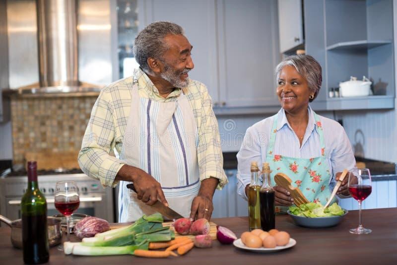 谈话微笑的夫妇,当在家时准备食物 免版税库存图片
