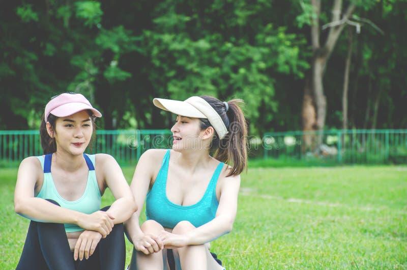 谈话快乐的年轻女人的画象坐瑜伽席子和,当有断裂时在训练以后在体育场 图库摄影