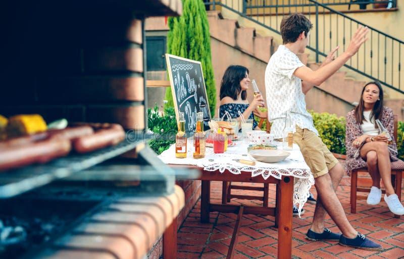 谈话烹调在熔炉的青年人户外和膳食 免版税库存图片