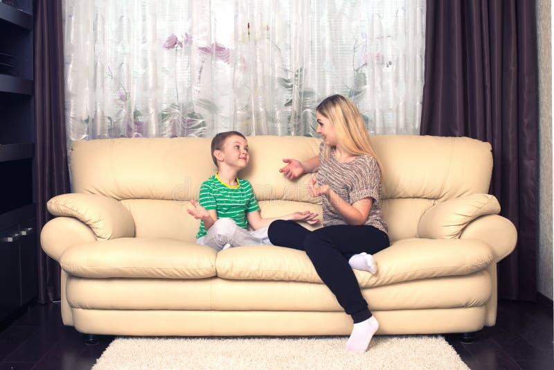 谈话的母亲和的儿子在家坐和,家庭时间 库存图片