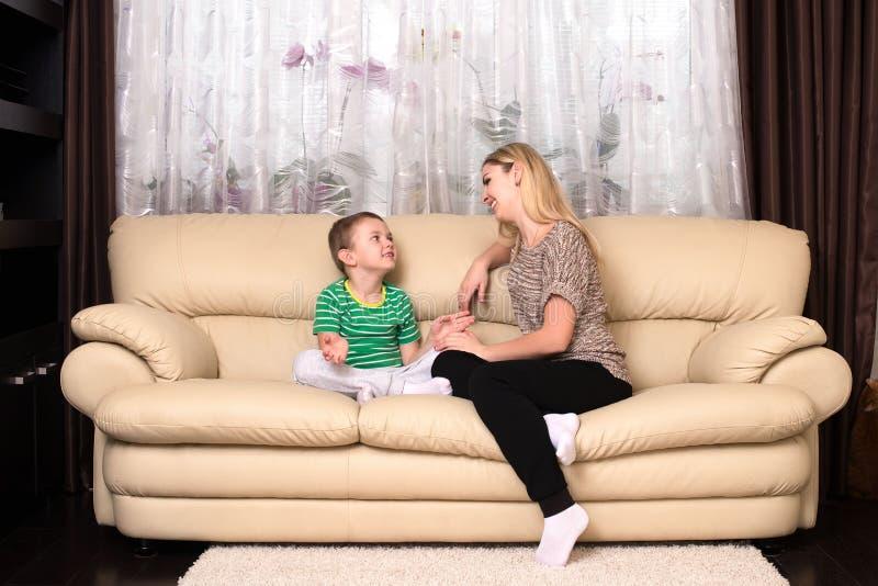 谈话的母亲和的儿子在家坐和,家庭时间 库存照片