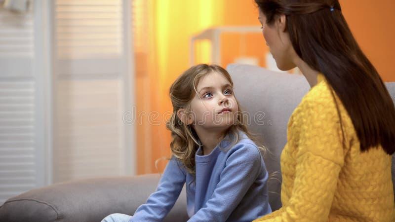 谈话的母亲和的女儿,解释如何的妈妈表现在生活情况 免版税库存照片