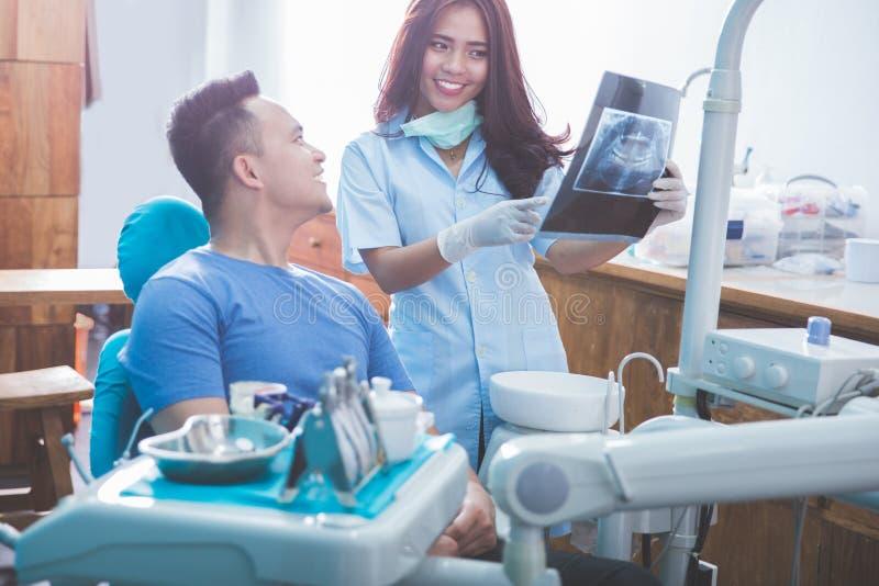谈话的牙医显示他的x光芒射线照相的患者 免版税图库摄影
