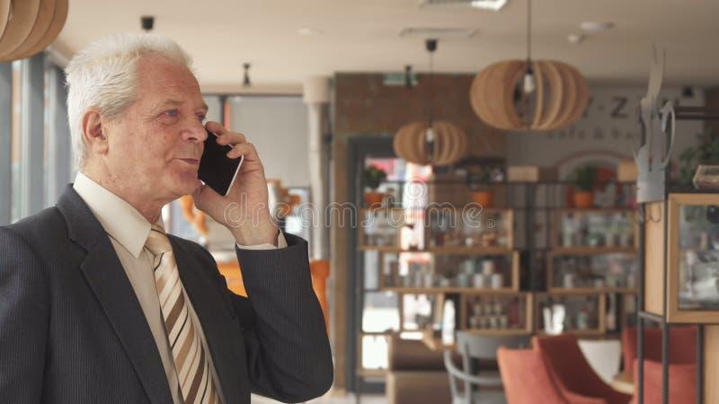 谈话的资深商人fininshes在电话在咖啡馆 免版税库存照片