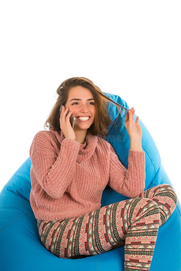 谈话笑的逗人喜爱的妇女坐蓝色装豆子小布袋主持和  免版税库存图片