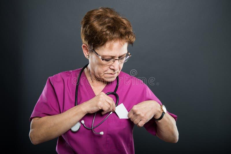 谈话资深夫人的医生投入名片 免版税库存照片